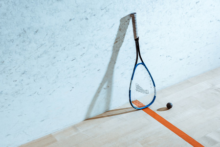 Raqueta de squash y pelota sobre piso de madera en cancha de cuatro paredes