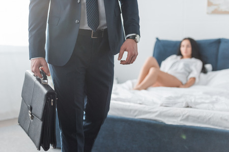 cropped view of businessman holding briefcase while standing in bedroom near woman Stockfoto
