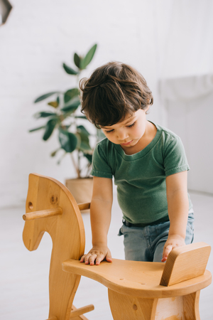 Toddler boy in green t-shirt and wooden rocking horse