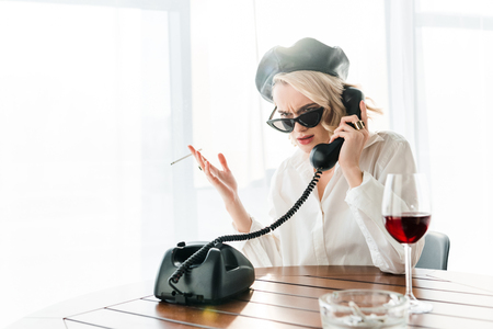 Elegant dissatisfied blonde woman in black beret and sunglasses smoking cigarette while talking on retro phone near glass of red wine