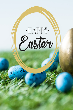 Blue painted quail eggs on green grass near golden chicken egg and happy Easter lettering in circle Imagens