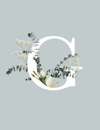 White letter C with wildflowers, buds and green leaves isolated on grey background Stock Photo