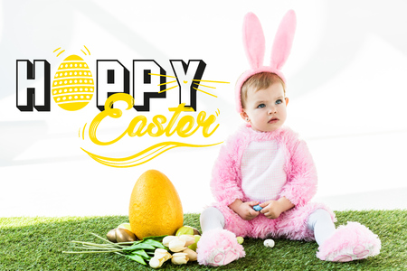 Cute baby in bunny costume sitting near colorful chicken eggs, tulips and yellow ostrich egg with happy Easter lettering Imagens