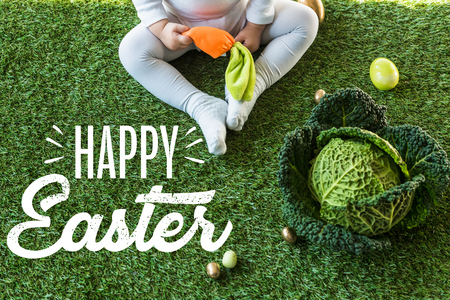 Partial view of child holding toy carrot while sitting near Easter eggs and savoy cabbage on green grass with happy Easter lettering