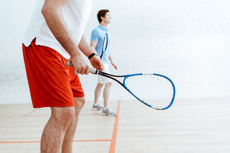 Partial view of two squash players with rackets in four-walled court