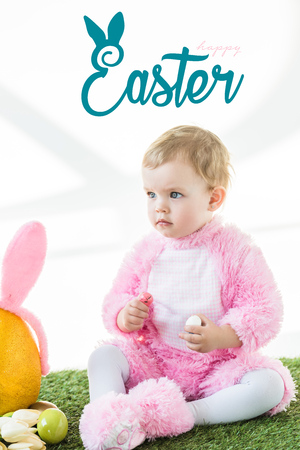 Cute baby in bunny costume sitting on green grass with happy Easter lettering above