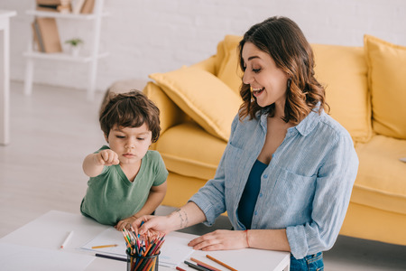 Excited mother and son drawing with color pencils in living room