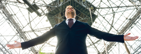 panoramic shot of joyful businessman with outstretched hands in greenhouse Stock Photo