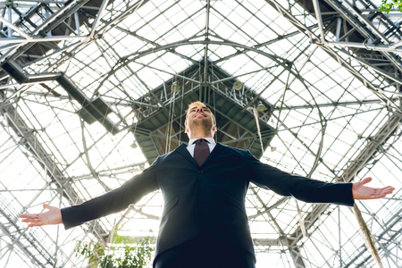 low angle view of joyful businessman with outstretched hands in greenhouse