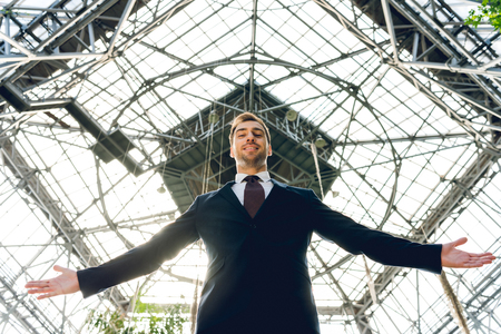 low angle view of joyful businessman with outstretched hands standing in greenhouse Imagens