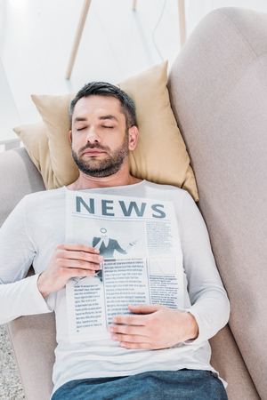 Handsome bearded man with eyes closed holding newspaper and resting on couch at home