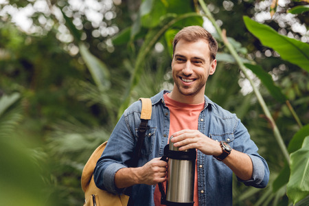Selective focus of smiling traveler with backpack opening thermos in tropical forest Archivio Fotografico