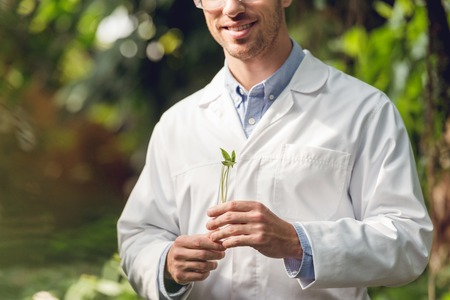 Cropped view of happy scientist in white coat and goggles holding flask with plant sample in orangery