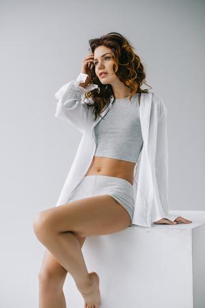 Verträumte lockige junge Frau, die Haare berührt, während sie auf weißem Hintergrund sitzt