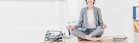 panoramic shot of businesswoman in suit sitting on desk and meditating in Lotus Pose in office