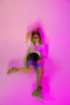 Motion blur of young woman in sunglasses lying on purple background