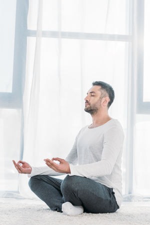 Handsome man with eyes closed sitting on carpet in Lotus Pose and meditating at home Stock Photo