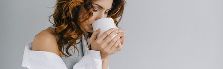 Panoramic shot of pretty curly girl drinking coffee on grey background