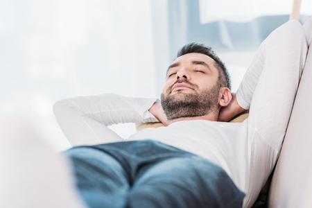 Selektywne skupienie przystojnego brodatego mężczyzny odpoczywającego z zamkniętymi oczami