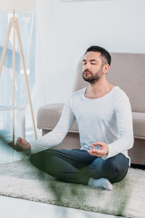 Selective focus of handsome man sitting on carpet in Lotus Pose and meditating at home