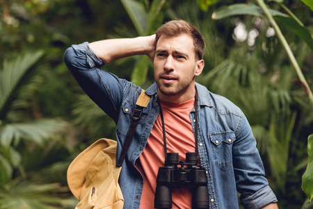 Handsome tense traveler with binoculars and backpack in green tropical forest Stock Photo