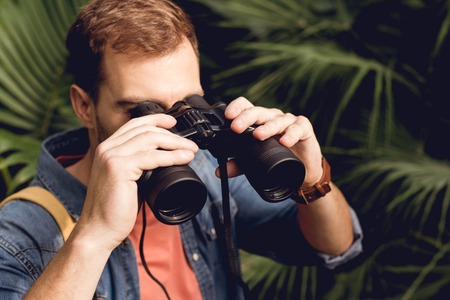 Handsome adult tourist looking through binoculars in tropical forest