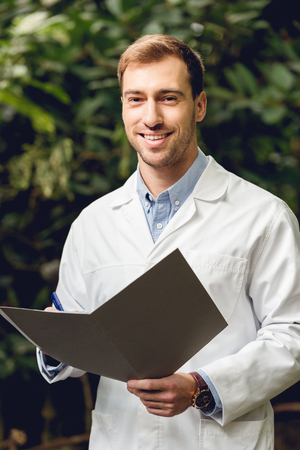 Smiling scientist in white coat holding journal in green orangery