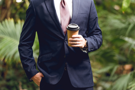 Cropped view of businessman in suit and tie holding coffee to go in orangery