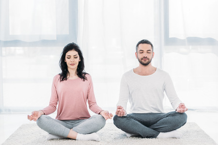 Woman and man with eyes closed sitting in Lotus Pose and meditating at home