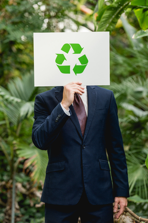 Businessman in suit holding card with green recycling sign in front of face in greenhouse Stock fotó