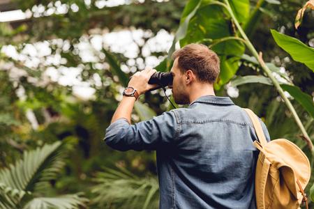 Turista adulto con mochila mirando a través de binoculares en el bosque tropical