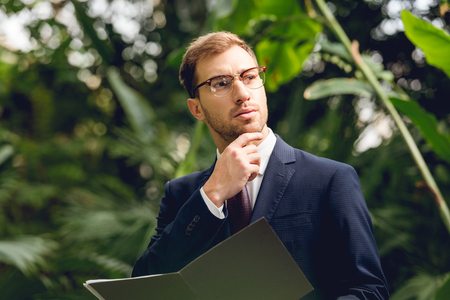 Dreamy businessman in suit and glasses holding folder in greenhouse