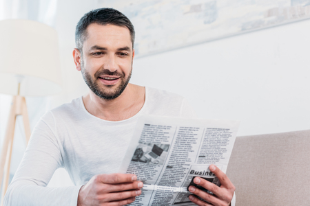 Handsome smiling bearded man reading newspaper at home Banco de Imagens - 121966465