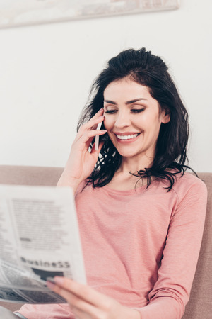 Selective focus of beautiful smiling woman talking on smartphone and reading newspaper at home