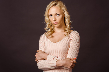 upset blonde woman standing with crossed arms isolated on black