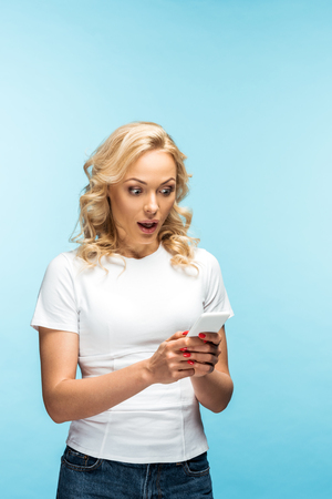 shocked blonde woman looking at smartphone and standing on blue 版權商用圖片
