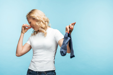 curly blonde woman touching nose while holding smelly dirty sock on blue