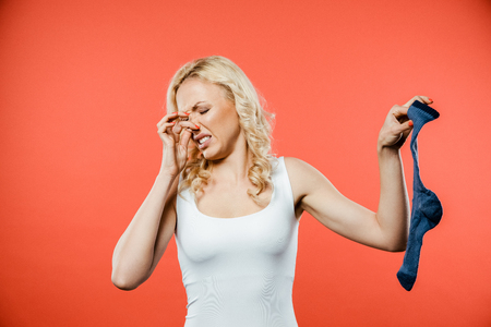 curly blonde woman touching nose while holding smelly dirty sock on red