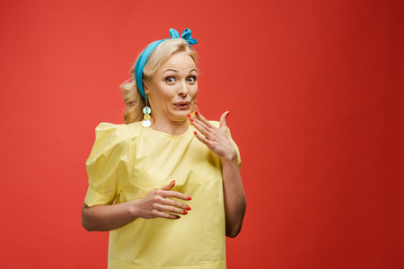 cheerful blonde woman in blue headband looking at camera and gesturing on red