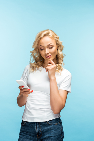 pensive and attractive blonde woman looking at smartphone on blue Stock fotó