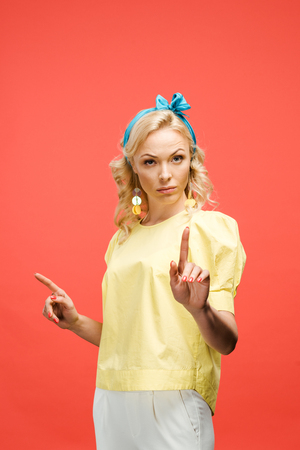 serious blonde woman looking at camera and pointing with fingers on red Stock fotó