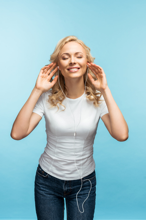 cheerful woman with closed eyes listening music in earphones on blue Archivio Fotografico