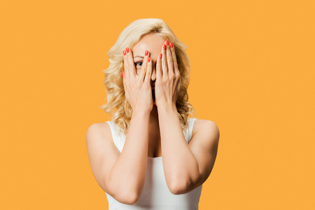 curly blonde woman covering face and looking at camera isolated on orange