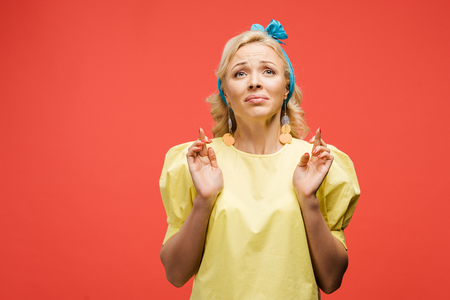 sad blonde woman in blue headband standing with fingers crossed on red Banque d'images - 122143631