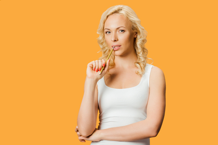 blonde woman holding pencil near mouth while thinking isolated on orange