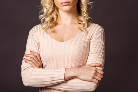 cropped view of serious woman standing with crossed arms isolated on black Stock Photo - 122161041
