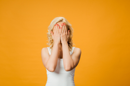 curly blonde woman covering face while standing isolated on orange