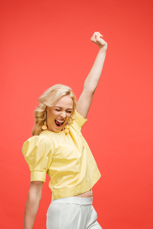 happy blonde woman with closed eyes celebrating success on red Stock Photo - 122242910