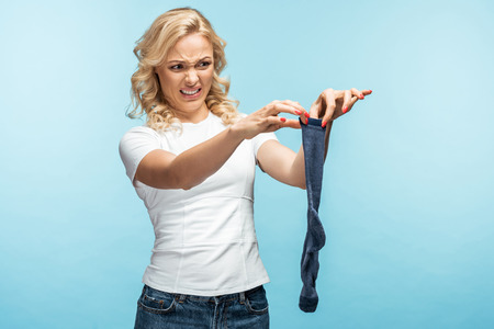 attractive curly blonde woman looking at disgusting sock on blue 스톡 콘텐츠