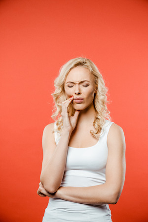 attractive woman with closed eyes having toothache on red Reklamní fotografie